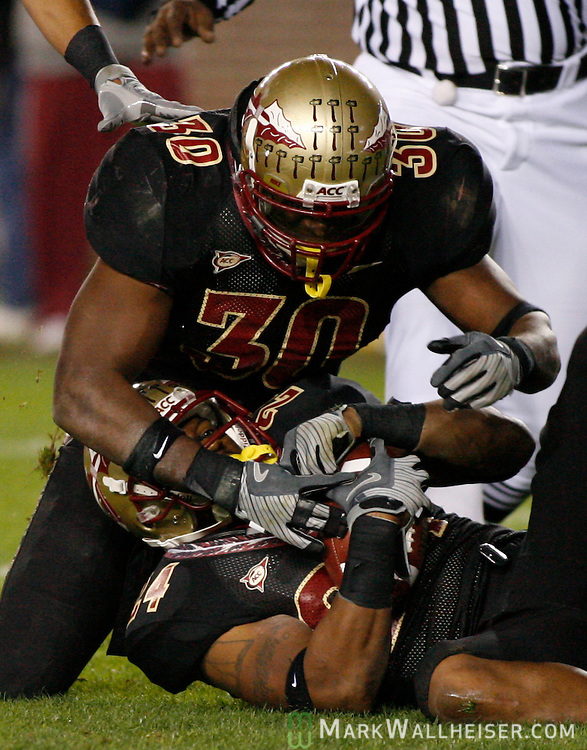 FSU linebacker Derek Nicholson (30) celebrates with Darius McClure after McClure intercepted a Boston College pass in the 2nd half of Florida State's NCAA football game against  Boston College at Bobby Bowden field on the Florida State University campus in Tallahassee, Florida November 15, 2008.  (Mark Wallheiser/TallahasseeStock.com)