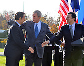Camp David, MD - October 18, 2008 --  United States President George W. Bush, center, gestures towards the golf carts after President Nicolas Sarkozy of France, who also serves as this year's rotating President of the European Union (EU),left and President José Manuel Barroso of the European Commission (EC), right, shook hands at the Presidential Retreat near Thurmont, Maryland for talks on Saturday, October 18, 2008.  The two European leaders stopped at Camp David to meet with President Bush to discuss the economy on their way home from a summit in Canada to try to convince Bush to support a summit by year's end to try to reform the world financial system..Credit: Ron Sachs / Pool via CNP