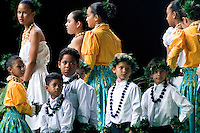 Boy and girl hula dancers wait on the sidelines before a modern hula performance.