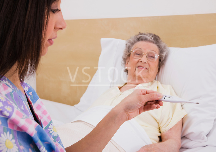 Nurse checking temperature on thermometer at female patients bed