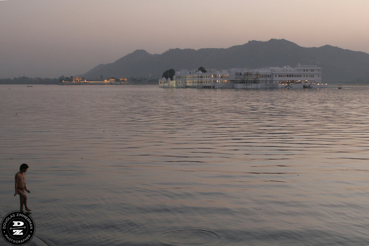 """A man dips his toe in Pichola Lake as the sun sets behind the Lake Palace Hotel, which sits on Jagniwas Island in the center of Pichola Lake, in Udaipur, Rajasthan, India.  Udaipur is located in a valley surrounded by the Aravalli hills, and at its center is the Pichola Lake.  The scenic city has been described as """"the most romantic spot on the continent of India"""" (by Colonel James Tod).  Photograph by Douglas ZImmerman"""