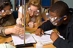 Education High School chemistry lab science class three students working together, female students taking an active role