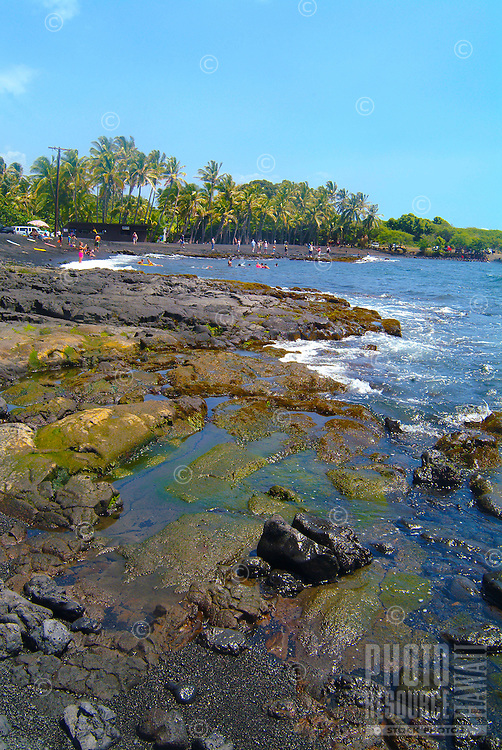 Many beachgoers enjoy the black sand beach at Punalu'u, Big Island.