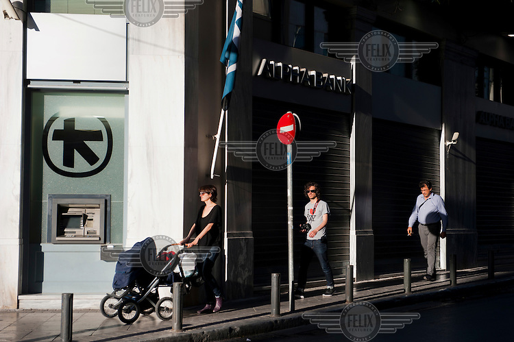 People pass by Alpha Bank on Mitropoleos Street, Athens.
