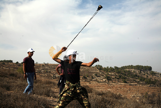 A Palestinian boy uses a slingshot to hurl stones towards Israeli soldiers stand guard during a demonstration by Palestinian, Israeli and foreign activists against the demolishing of farm land to be used in the construction of Jewish settlements near the existing Israeli settlement of Bat Ayin near the Palestinian village of Beit Omar, just north of the West Bank town of Hebron on November 13, 2010. Photo by Najeh Hashlamoun
