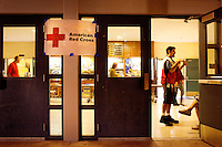 Santa Barbara, Calif., May 5, 2009 - Dominic Ventura, an EMT and pharmacy technician with the Red Cross, talks to an evacuee at the Red Cross Emergency Shelter at Dos Pueblos High School in Goleta, Calif. Even though around 1,000 homes were mandatorily evacuated, the shelter had only about twelve evacuees as of 10:30 pm. According to David Sadecki with the Santa Barbara County Fire Department, the fire began at around 1:45 pm today near the popular Jesusita Trail near Inspiration Point in San Roque Canyon. As of midnight more than 420 acres had burned and about 1,000 homes were evacuated, with about 2,000 threatened.