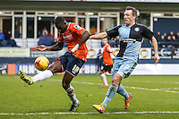 Magnus Okuonghae of Luton Town clears the ball under pressure from Garry Thompson of Wycombe Wanderers during the Sky Bet League 2 match between Luton Town and Wycombe Wanderers at Kenilworth Road, Luton, England on 26 December 2015. Photo by David Horn.