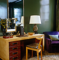 A Murano glass lamp sits on a Paul Frankl desk in the richly coloured bedroom