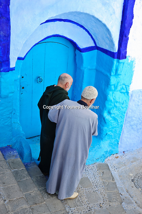 A man helps an elderly man walk down steep stairs in Chefchouen
