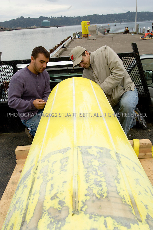 10/11/2007--Newport, OR, USA..Oregon State University researchers  Adam Brown (right) and Al Schacher(left) work to prepare the wave energy buoy the team will be deploying off the coast of Oregon in the Pacific Ocean...After waiting out a week of stormy seas, Oregon State University researchers launched the first test run of their wave energy buoy Saturday, October 12th. The buoy is the fifth prototype Oregon State University engineering professor Annette von Jouanne's team has built, and the first tested by OSU in open seas. Previous testing has been done in labs and in Yaquina Bay, von Jouanne said...The buoy was towed to a point about 21/2 miles offshore from Newport,.and returned later in the day. ..©2007 Stuart Isett. All rights reserved.