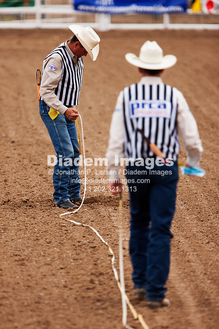 BELLE FOURCHE, SOUTH DAKOTA - JULY 4:  Rodeo officials use a tape measure before the start of the 90th annual Black Hills Roundup rodeo on July 4, 2009 in Belle Fourche, South Dakota.  (Photograph by Jonathan P. Larsen)
