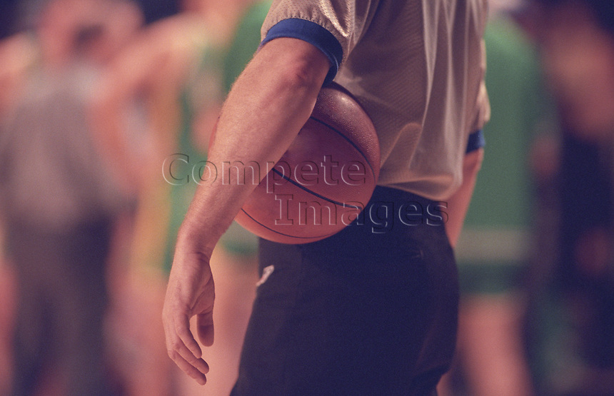 Referee holding basketball under his arm