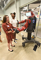 NWA Democrat-Gazette/FLIP PUTTHOFF <br /> Abby Lopez (left) and Kali Corbin, students at Bentonville West High School, show guests on Wednesday how Baxter the robot works during the opening of Ignite professional studies program in Bentonville. Ignite students hone their skills in a number of career fields.