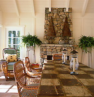 View along the folk-art table towards the fieldstone fireplace flanked by a pair of French Directoire pedestals in the covered porch