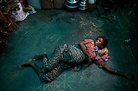 Roma Hattu, a nine month pregnant Rohingya Muslim woman displaced by violence grimaces in labor pain on the bare floor of a former rubber factory now serving as her family shelter near Sittwe April 28, 2013. Picture taken April 28, 2013.   REUTERS/Damir Sagolj (MYANMAR)