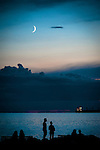 A crescent moon with silhouetted people at a beach during the blue hour.