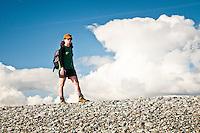 A female hiker on a beach near Okarito - Westland National Park, West Coast, New Zealand