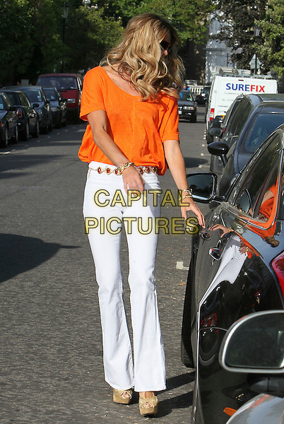 ELLE MACPHERSON .pictured in London, England, UK, .May 3rd 2011..full length jeans wide leg flares white denim orange t-shirt tee top   belt curly hair  wavy platform shoes peep toe beige cream  gold bracelets getting into car door wedges .CAP/HIL.©John Hillcoat/Capital Pictures