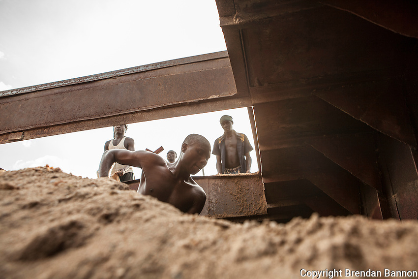 Men dig sand from a  cargo boat at a small port in Kibuye, Rwanda on Lake Kivu. Brendan Bannon. March 1, 2014