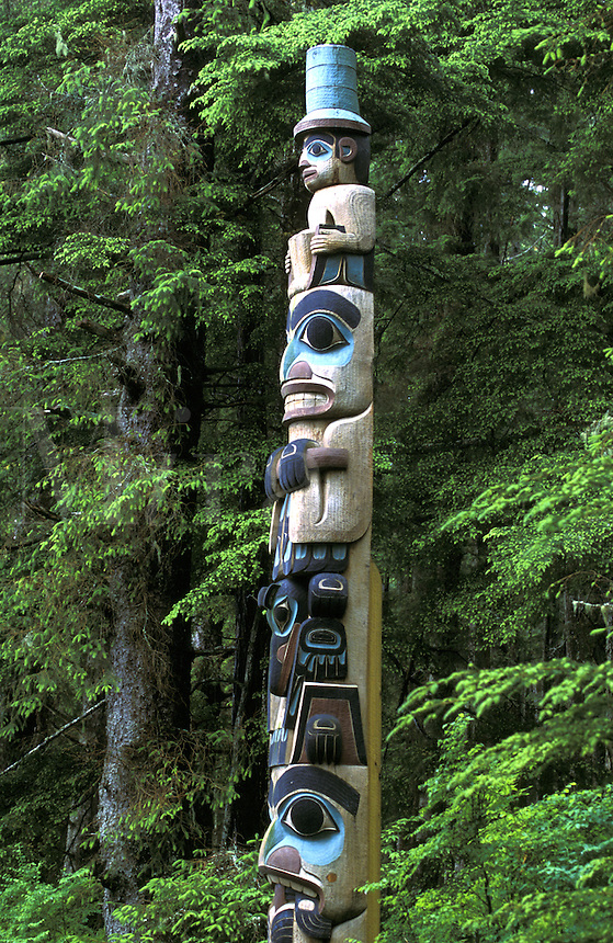 Yaadass Crest Corner Pole, This pole stood at one of the exterior corners of the Yaadass clan house.  The human figure at the top is the Village Watchman.  Below the Watchman is Raven in human form.   The next figure is also Raven, while the base figure appears to be a bear holding an animal of some type in its mouth.  Figures below the Village Watchman may be crests of the clan who owned the house and could represent incidents in the real or mythical history of the clan.  The pole is a copy carved by Tlingit artist Tommy Jimmie in 1978 to replace the original collected in 1903.  It is believed to be a crest pole portraying the heraldic emblems of the Yaadaas clan of Old Kasaan.??Sitka National Historical Park, Sitka, Alaska.