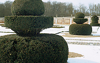 A snow-covered sunken garden fashioned to resemble a chessboard is scattered with topiary hedges clipped in the shape of chess pieces