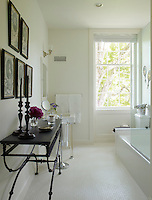 A contemporary bathroom is decorated with antique black and white prints and a painted metal table