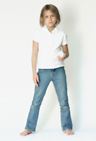shoeless blonde girl in blue jeans and white shirt holds white rat