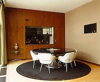 In the dining room the glass topped round dining table by Patrick Gwynne is surrounded by Saarinen chairs and the splashback is by Stefan Knapp