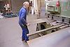 Man shearing plate using machine at engineering works,