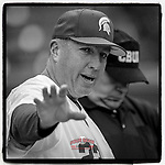 Head coach Jake Boss Jr. (23) of the Michigan State Spartans meets with the umpires before a game against the Connecticut Huskies on Friday, March 15, 2019, at Fluor Field at the West End in Greenville, South Carolina. Connecticut won, 10-6. (Tom Priddy/Four Seam Images)