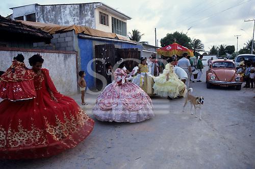 Recife, Brazil. Women in traditional brightly coloured Maracatu hooped costume dresses preparing for the enthronement of a Maracatu princess. Pernambuco State.