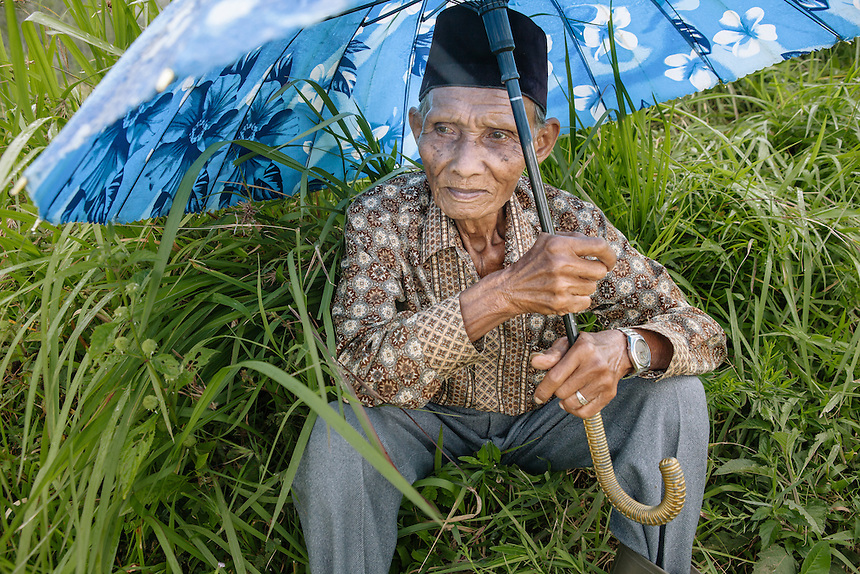 An old man waits at the side of the Pacu Jawi's arena.