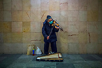 Busker wearing a protective face mask plays the violin in the subway at Nyugati Square during the coronavirus emergency in Budapest, Hungary, March 18, 2020. (Zoltan Balogh/MTI via AP)