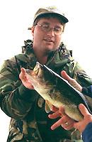 Proud fisherman age 30 displaying Large Mouth Bass caught on Roy Lake.  Nisswa Minnesota USA