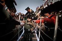 Catania, 18 Marzo, 2002. Un bambino curdo viene aiutato a sbarcare al suo arrivo nel porto di Catania.