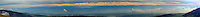 Super-Panoramic view of Swiss Alps and lowlands under swirling golden skies.<br />