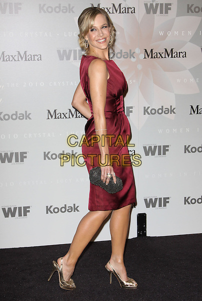 JULIE BENZ.2010 Crystal + Lucy Awards: A New Era_Arrivals held at The Hyatt Century Plaza Hotel, Century City, CA, USA..June 1st, 2010 .full length dress side gold shoes red burgundy maroon silk satin sleeveless clutch bag .CAP/ADM/KB.©Kevan Brooks/AdMedia/Capital Pictures.