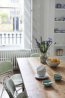 Metal wire kitchen chairs have been covered with a green and white scalloped pattern