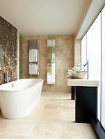A modern tiled bathroom in neutral tones. Two steel washbasins sit on a deep granite plinth and a freestanding bath stands to one side of room.