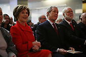 United States President George W. Bush, center, looks on during the ceremony marking the reopening of the National Museum of American History in Washington, DC on November 19, 2008. After the ceremony five people were sworn in as new citizens of the United States.  First lady Laura Bush attended with the President is at left. <br /> Credit: Gary Fabiano / Pool via CNP