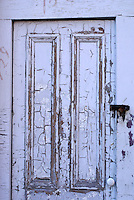 Old wooden door with peeling white paint in the city of Saint John, New Brunswick, Canada
