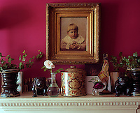 On the living room mantelpiece two small carved pugs glower from under a gilt-framed child's portrait