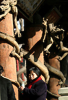 Tourists and worshippers stand under columns of intricately carved dragons at the Jin Ancestral Temple near Taiyuan, Shanxi Province, China. The Jin Temple is one of the oldest architecture complex in China, originating as far as 500 A.D. during the Northern Wei Dynasty and saw various renovations and expansions in successive dynasties..08-FEB-04