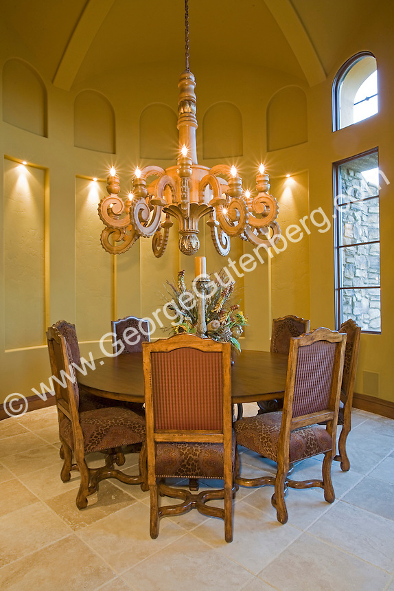 Impressive round formal dining room with vaulted ceiling and large wooden chandelier, and arched windows Stock photo of residential dining room