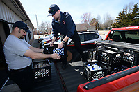 NWA Democrat-Gazette/ANDY SHUPE<br /> Keith Andrews (left) and Dillan Jones, both firefighters with the Farmington Fire Department, work together Friday, March 22, 2019, to unload milk at the Farmington Senior Center for use in today's annual pancake breakfast at the department's fire station. The fundraising breakfast, planned for 6 to 10 a.m. today, is expected to serve about 1,000 people and raises money for the purchase of equipment for the department.
