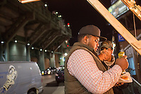 Imani Sweeney (black hat) and Rich Webb prepare their hotdogs after buying them from a street vendor across Lansdowne Street from Fenway Park in Boston, Massachusetts, USA, in the early hours of Saturday, Dec. 5, 2015.
