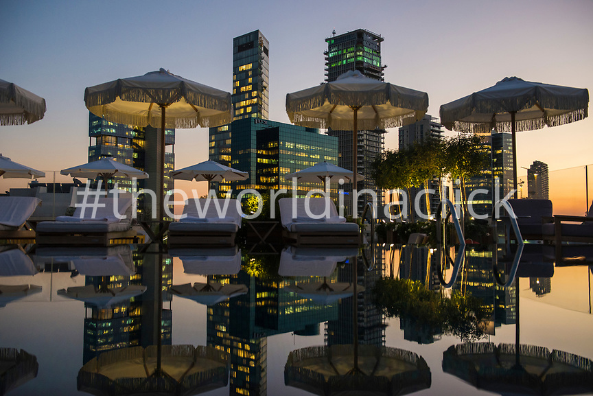 ISRAEL, Tel Aviv, a view of The Norman's Hotel infinity pool during sunset. Office Buildings in the background