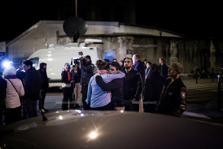 Paris, France, 15.11.2015. An american couple conforts eachother in front of Le Carillon, on of the many bars that were struck by the attack. Images from Paris in the aftermath of the devastating terror attacks on friday november 13. Photo: Christopher Olssøn.