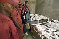 Rwanda. Southern province. Murambi. A group of teenagers and young men look at the skeletons of Tutsis, killed during the 1994 genocide. Mortal remains laid on wood boards at the Genocide Memorial. Over 50'000 people perished on the site and thrown in mass graves. The site of Murambi is located in the district of Nyamagabe, in the former Gikongoro prefecture, Nyamagabe commune. The site of Murambi is intented to be a regional research and documentation centre on Genocide. A special memory place. © 2007 Didier Ruef