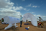 Refugees and workers for the ACT Alliance pitch tents provided by the United Nations for newly arrived refugee families in the Dadaab refugee camp in northeastern Kenya. Tens of thousands of refugees have fled drought-stricken Somalia in recent weeks, swelling what was already the world's largest refugee settlement. The Lutheran World Federation--a member of the ACT Alliance--manages the camp, and is working with UN agencies in helping receive and house the new refugees.